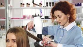 Professionele kapper die bij haar salon drogend haar werken van haar vrouwelijke cliënt stock afbeelding