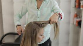 Professionele kapper die kammend modelhaar stileert Mooie vrouw in salon stock videobeelden