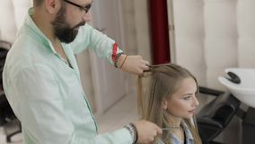 Professionele kapper die kammend modelhaar stileren Mooie vrouw in salon stock video