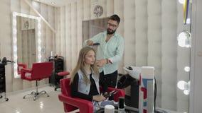 Professionele kapper die kammend modelhaar stileren Mooie vrouw in salon stock footage