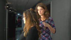 Professionele kapper die kapsel met broodje en krullen voor mooi gezond haar in een schoonheidssalon doen stock videobeelden