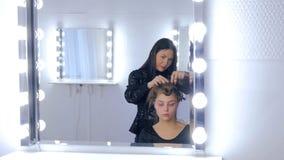 Professionele kapper die kapsel voor jonge mooie vrouw doen Stock Foto