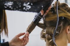 Professionele kapper die kapsel voor jonge mooie vrouw doen die - krullen maken Stock Foto