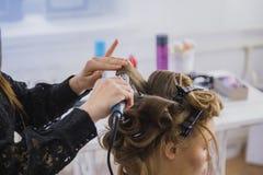 Professionele kapper die kapsel voor jonge mooie vrouw doen die - krullen maken Stock Afbeeldingen