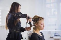 Professionele kapper die kapsel voor jonge mooie vrouw doen die - krullen maken Stock Foto's