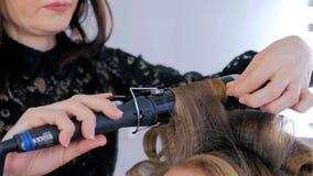 Professionele kapper die kapsel voor jonge mooie vrouw doen die - krullen maken Royalty-vrije Stock Foto's