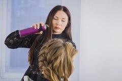 Professionele kapper die kapsel voor jonge mooie vrouw met lang haar doen Royalty-vrije Stock Afbeelding