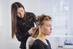 Professionele kapper die kapsel voor jonge mooie vrouw met lang haar doen Stock Foto's