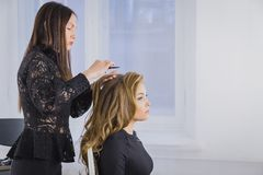 Professionele kapper die kapsel voor jonge mooie vrouw met lang haar doen Royalty-vrije Stock Afbeeldingen