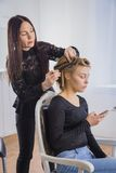 Professionele kapper die kapsel voor jonge mooie vrouw met lang haar doen Royalty-vrije Stock Fotografie