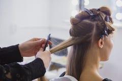 Professionele kapper die kapsel voor jonge mooie vrouw met lang haar doen Stock Afbeelding