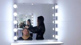 Professionele kapper die kapsel voor jonge mooie vrouw met lang haar doen Royalty-vrije Stock Foto's
