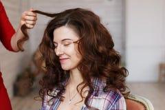 Professionele kapper die krullen van een donkerbruin meisje maken royalty-vrije stock afbeeldingen