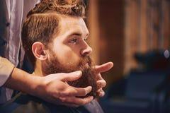 Professionele kapper het stileren baard van zijn cliënt royalty-vrije stock afbeeldingen