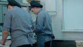 Professionele keuken met bezig team van koks en chef-kok die maaltijd voorbereiden stock footage
