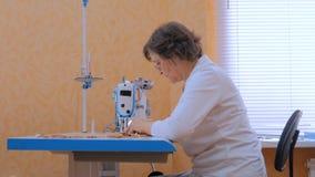 Professionele kleermaker, de naaiende kleren van de manierontwerper met naaimachine stock video