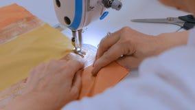 Professionele kleermaker, de naaiende kleren van de manierontwerper met naaimachine stock footage