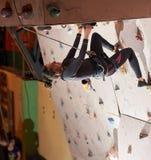 Professionele klimmer opleiding binnen op een rotsmuur Stock Afbeeldingen