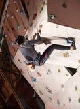 Professionele klimmer opleiding binnen op een rotsmuur Royalty-vrije Stock Afbeeldingen