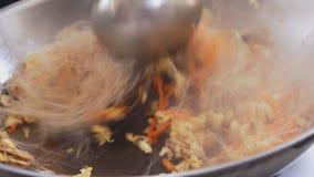 Professionele kok bradende noedels en groenten bij het festival van het straatvoedsel Proces om dicht omhoog te koken stock video