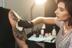 Professionele kunstenaar die gebeëindigde tatoegering met hygiënisch servet afvegen royalty-vrije stock foto's