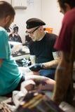 Professionele kunstenaar die kleurrijke tatoegering op cliëntbeen doen Royalty-vrije Stock Foto's