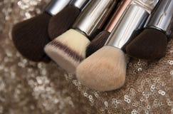 Professionele make-upborstels op roze lovertjeachtergrond stock fotografie