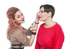 Professionele make-upkunstenaar die make-up maken aan een geïsoleerd model royalty-vrije stock afbeeldingen