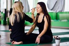 Professionele make-upkunstenaar die met mooie jonge vrouw werken geschiktheidsmodellen, aeroyoga Zit in de lotusbloempositie stock foto