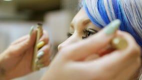 Professionele make-uppersoon een jong meisje met blauw haar stock footage