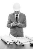 Professionele mannelijke architect die zijn slimme telefoon met behulp van stock afbeeldingen