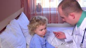 Professionele mannelijke arts die zijn kleine geduldige zitting van de meisjeskeel controleren op bed stock footage