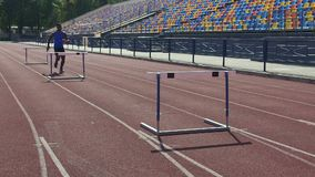 Professionele mannelijke atleet die gemakkelijk hindernissen, hindernissenras, training overwinnen stock footage