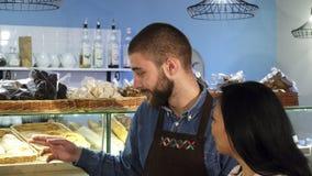 Professionele mannelijke bakker die bij zijn winkel werken die zijn rijpe vrouwelijke klant helpen stock afbeeldingen