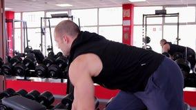 Professionele mannelijke bodybuilder die met zware domoren vóór de concurrentie uitoefenen stock video
