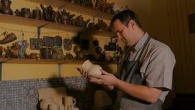 Professionele mannelijke pottenbakker die pot in aardewerkworkshop onderzoeken stock footage