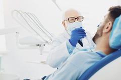 Professionele mannelijke tandarts die patiënt diagnostiseren stock foto