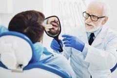 Professionele mannelijke tandarts die spiegel geven aan patiënt royalty-vrije stock afbeelding