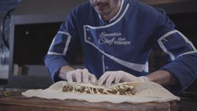 Professionele mens in blauwe chef-kok eenvormige het koken lulakebab in modern Turks restaurant Kok die kaas op zetten stock videobeelden
