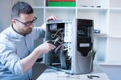 Professionele mens die en een computer herstellen assembleren Stock Foto's