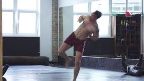 Professionele mmavechter opleiding bij de gymnastiek, die het spinnen hoge schoppen doen stock video