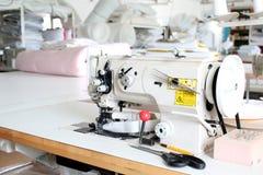Professionele naaimachine overlock in de workshop Materiaal om kleren in een kleermakerswinkel te scherpen te omzomen of te stikk stock foto
