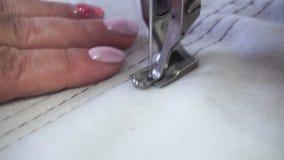 Professionele naaimachine, vrouwen` s handen op middelbare leeftijd stock footage