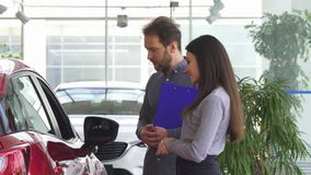 Professionele openings de autodeur van de autohandelaar voor zijn vrouwelijke cliënt stock footage