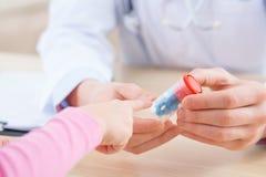 Professionele pediater die geneesmiddelen geven aan zijn patiënt stock afbeelding