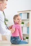 Professionele pediater die meisje onderzoeken stock afbeeldingen