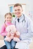 Professionele pediater die meisje onderzoeken stock foto