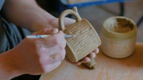 Professionele pottenbakker die patroon op kleimok maken met speciaal hulpmiddel in workshop stock videobeelden