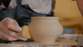 Professionele pottenbakkers snijdende pot met speciaal hulpmiddel in aardewerkworkshop stock footage