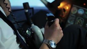 Professionele proef coördinerende vluchtdetails, die op radio aan controlemechanisme spreken stock footage